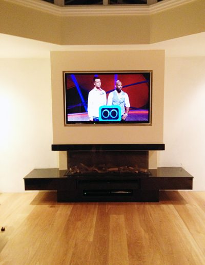 A contemporary black granite surround, fitted with a gas fire. We worked with media installation specialists to build this false chimney breast to accommodate both the unique fireplace and the TV system