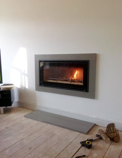 Grey granite contemporary surround and hearth, crafted by Millstone Designs and fitted with a wood burning stove