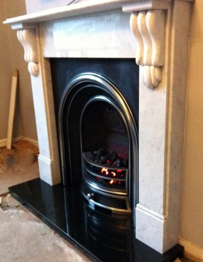 A traditional gas fireplace and surround, fitted with a boxed and lipped granite hearth crafted by Millstone Designs